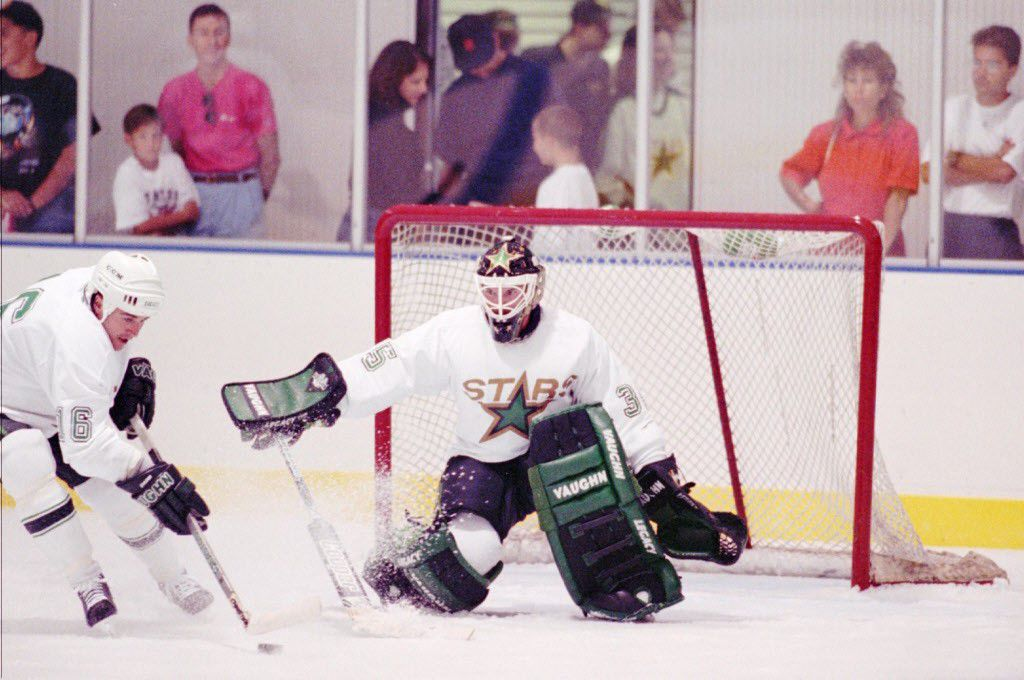 ORG XMIT: IRV102 Dallas Stars center Dean Evason (16) takes a shot as goalie Darcy Wakaluk (35) defends during a workout Sunday, Sept. 12, 1993, in Irving, Texas. Formerly the Minnesota North Stars, Dallas' newest professional sports team had a small crowd of onlookers for their first practice. (AP Photo/Pat Sullivan)