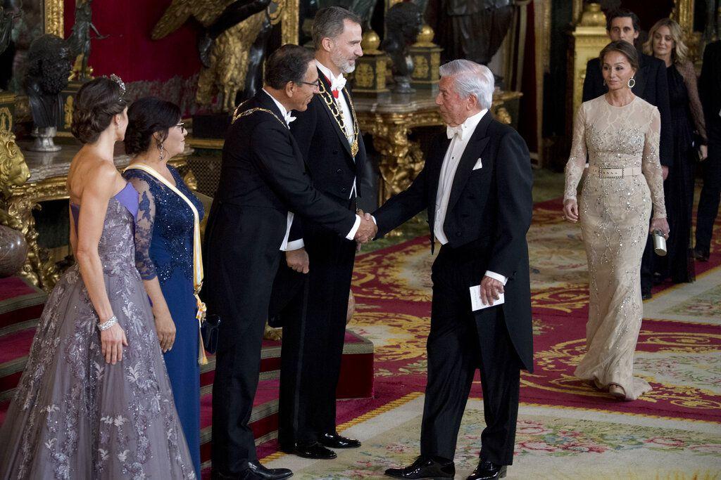 El presidente peruano Martín Vizcarra, tercero de la izquierda, se da la mano con el escritor peruano Mario Vargas Llosa, junto al rey Felipe VI de España, durante una cena oficial en el Palacio Real, en Madrid, el miércoles 27 de febrero del 2019. (Curto de la Torre/Pool Photo vía AP)