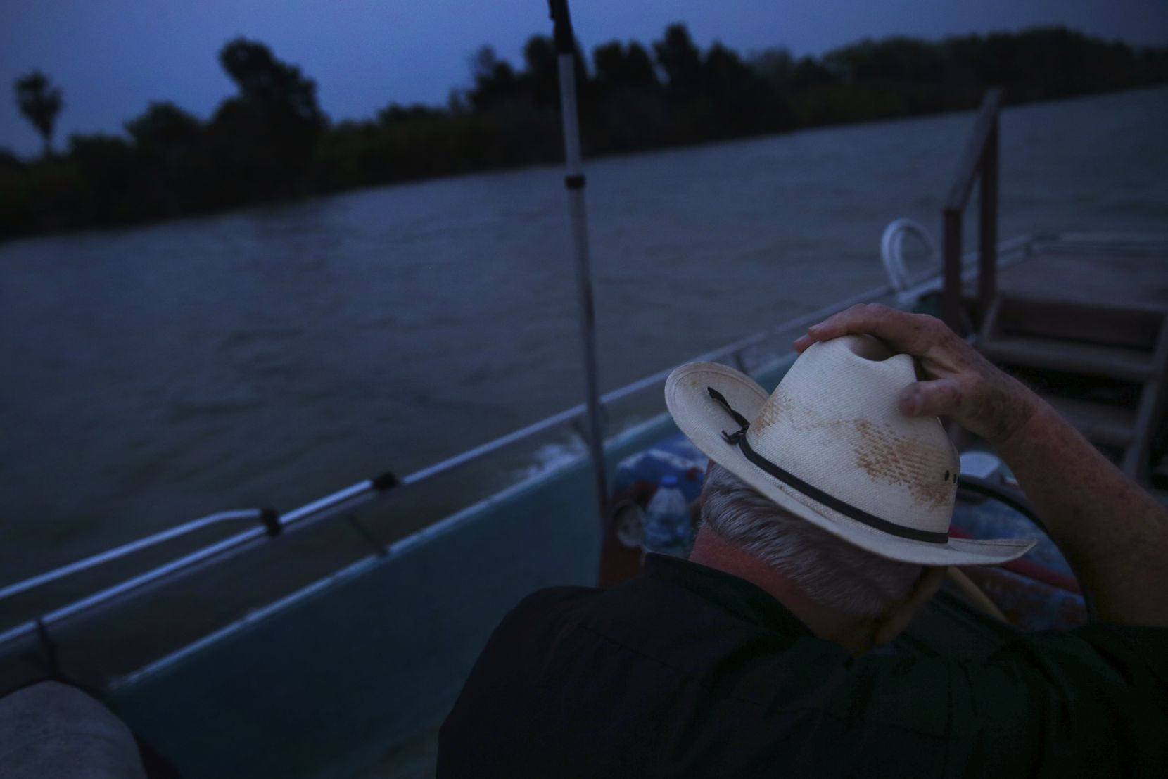 """Father Roy Snipes holds down his cowboy hat as the wind gusts while he motors down the Rio Grande. """"The river is a special place to me,"""" said Snipes. """"You look to the left and see Mexico and the United States on the right. It's surreal how close we are but so far apart."""""""
