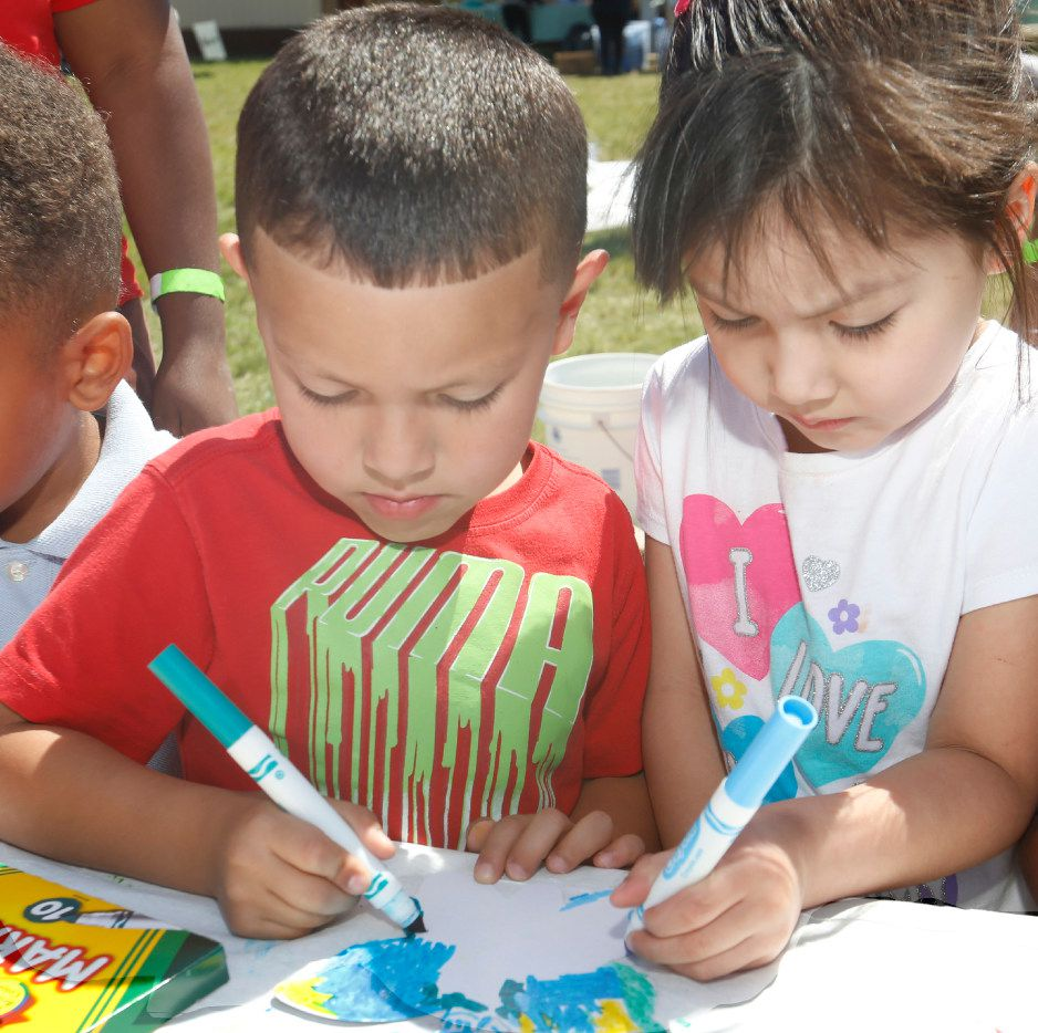 Stevens Park Elementary School pre-K student Israel Flores, 5, lets his sister, Natalie Flores, 4, help him color a butterfly cutout that will be hung in the schools outdoor classroom on May 5.