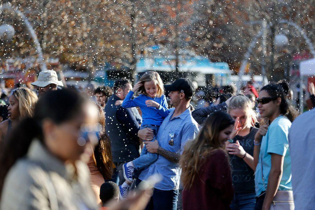 Josh Parman and his daughter James Parman, 6, enjoy the fake snow during the tree lighting celebration at Klyde Warren Park.