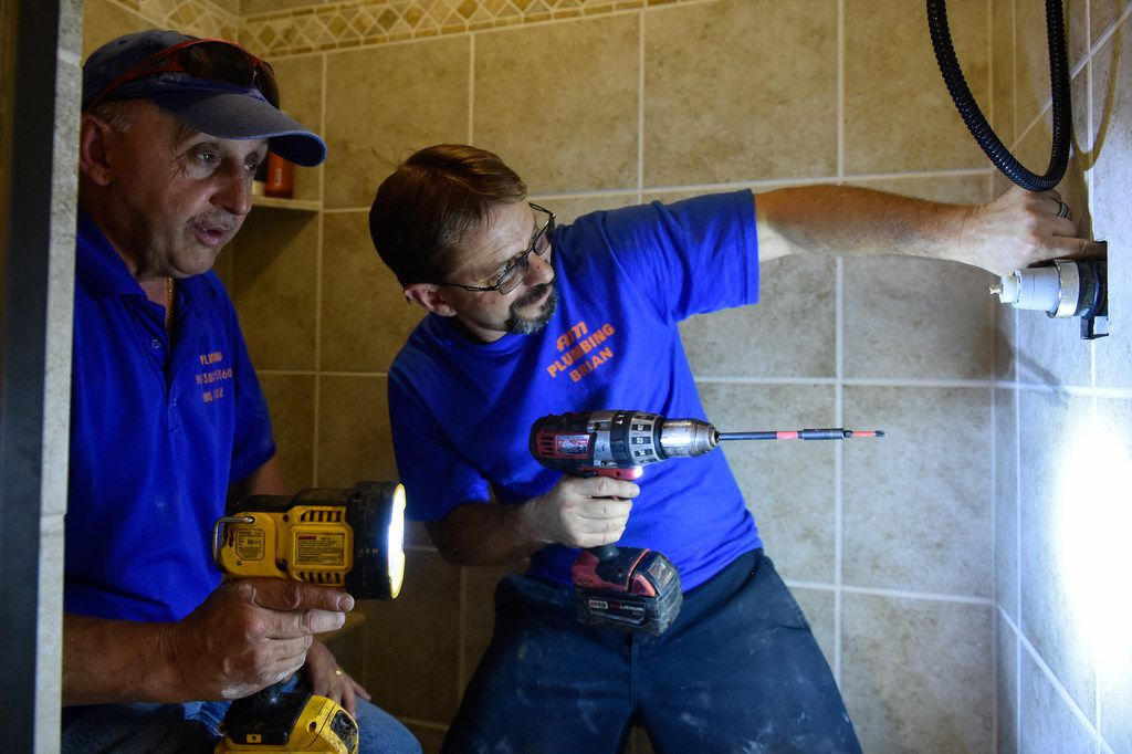 AM Plumbing co-owner Luis Lopez (left) and 10-year plumber Brian Robinson fix a low water pressure problem at a customer's house on May 31 in Denton.
