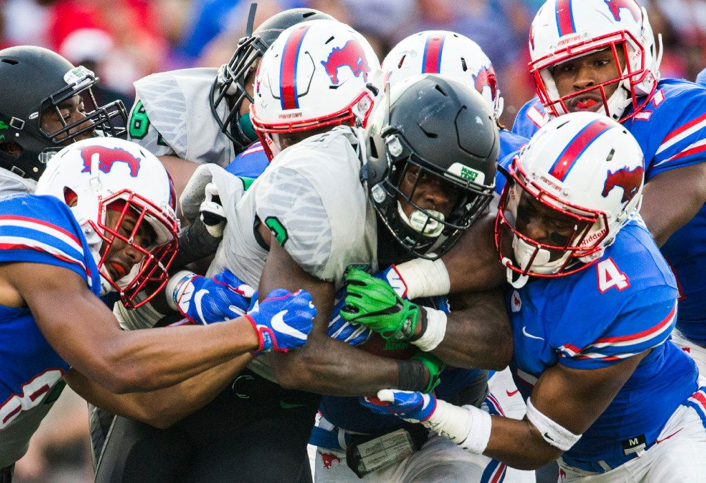 FILE - North Texas Mean Green running back Jeffery Wilson (3) is tackled by Southern Methodist Mustangs defenders during the second quarter of a football game between UNT and SMU on Saturday, September 9, 2017 at SMU's Ford Stadium in Dallas. (Ashley Landis/The Dallas Morning News)