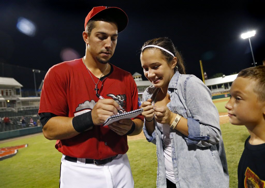 Jake Skole (left) signs an autograph for Angel Brazier, 13, after taking the ALS ice water challenge following their defeat of the Midland Rockhounds at Dr. Pepper Ballpark in Frisco on Saturday, August 30, 2014.  Winning bids got the opportunity to dump a bucket of ice water on the corresponding Frisco Roughriders baseball player. (Stewart F. House/Special Contributor)