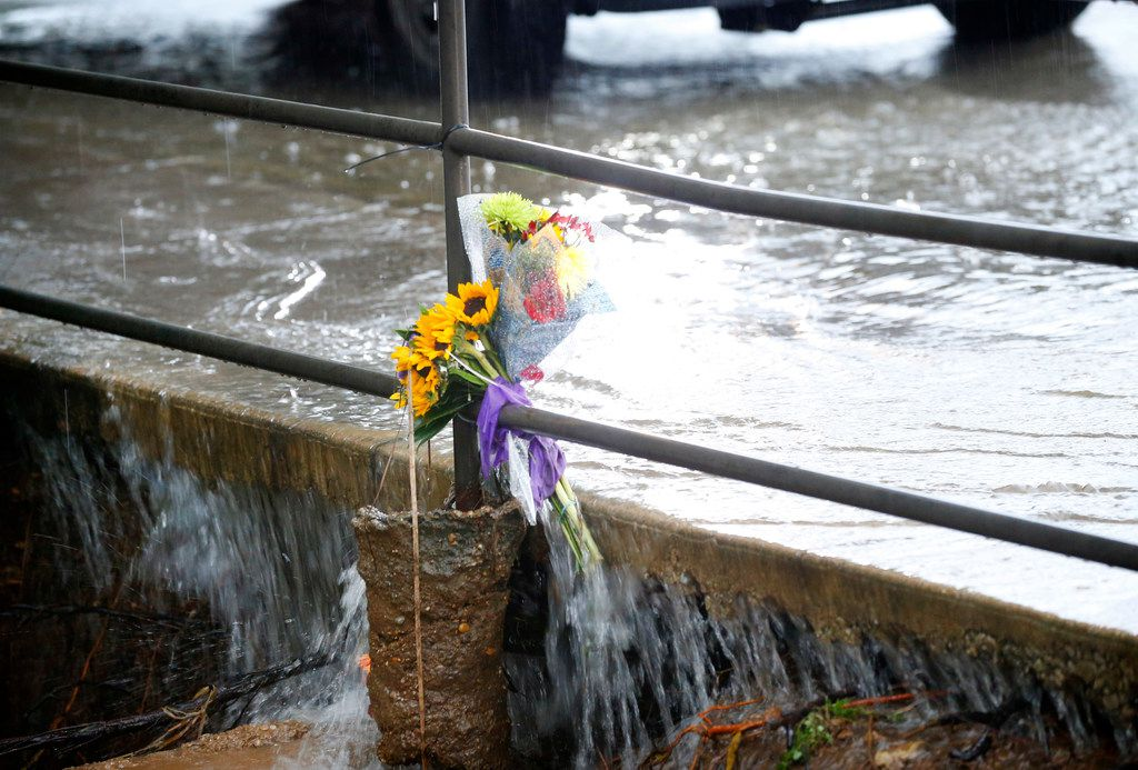 Flowers secured to a railing sustain the flooding rains on Greek Row Drive on the University of Texas at Arlington campus on Sept. 26, 2018. The flowers were left in memory of student Alan Amaya of El Paso, who was swept into a pipe after flooding rains struck the campus.