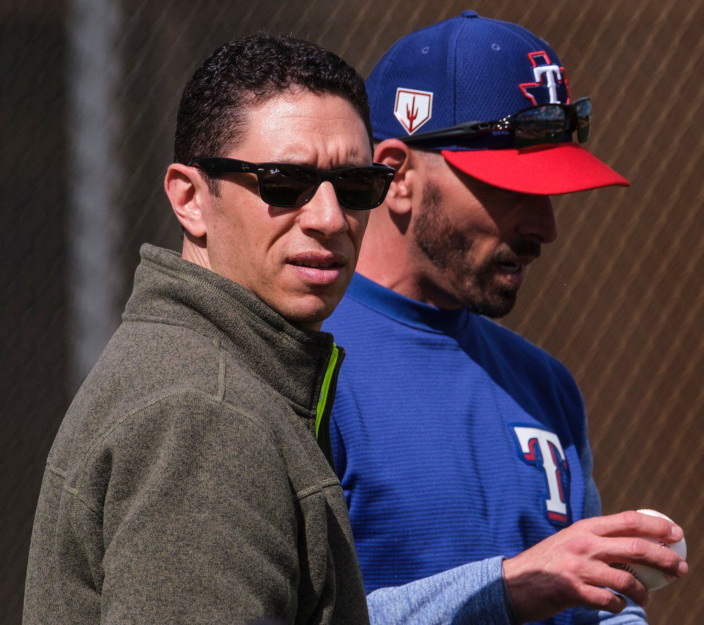 Texas Rangers general manager Jon Daniels (left) and manager Chris Woodward watch batting practice during the first full squad spring training workout at the team's training facility on Monday, Feb. 18, 2019, in Surprise, Ariz.. (Smiley N. Pool/The Dallas Morning News)