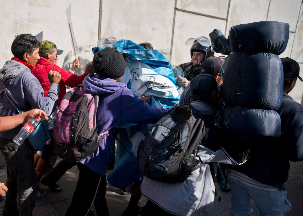 Migrants push past Mexican police at the Chaparral border crossing in Tijuana on Nov. 25, 2018, as they try to reach the U.S.