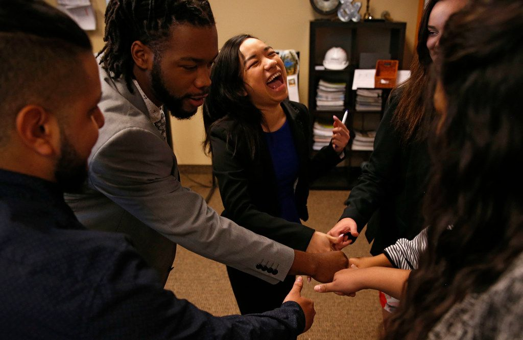 *Jonathan Devora (left) , Shaquille Thomas, Kim Hoang (center) and Hannah Magnuson break a group meeting with a cheer at Evantage.