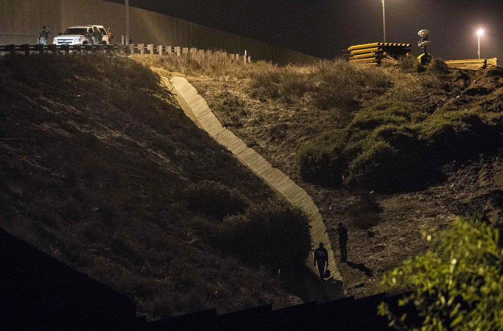Border Patrol agents look for Central American migrants hiding on the U.S. side of a fence on the Mexican border.