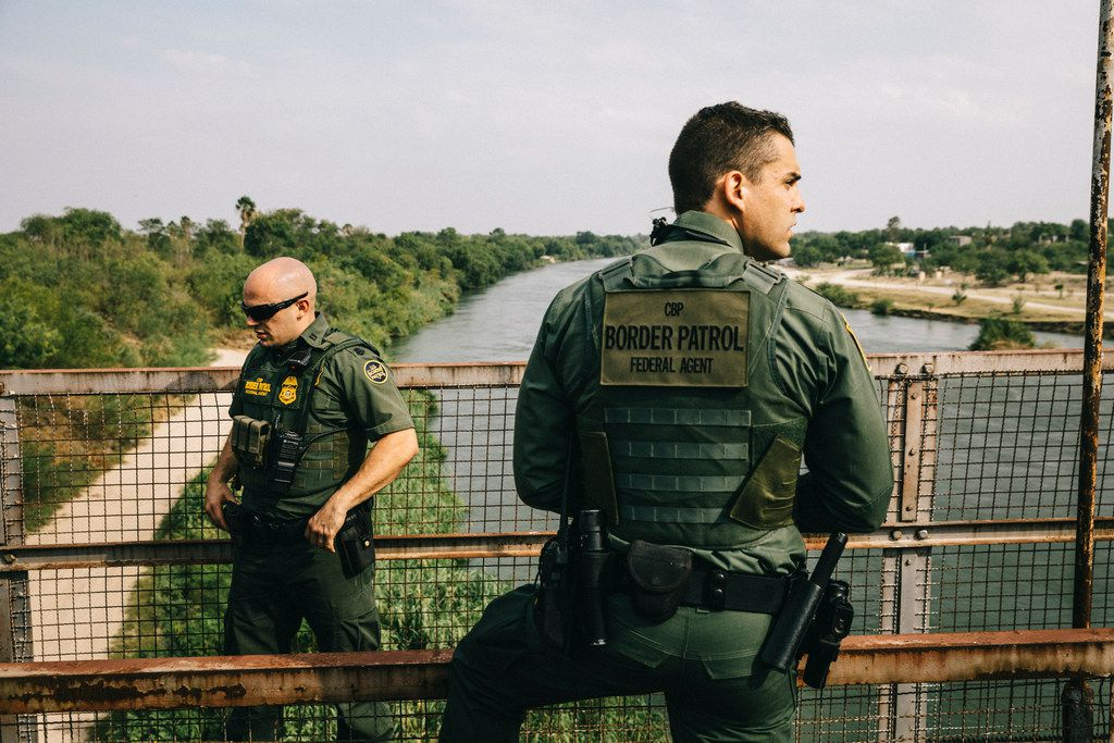 U.S. Border Patrol agents survey the Rio Grande River from an old bridge in Roma, Texas.