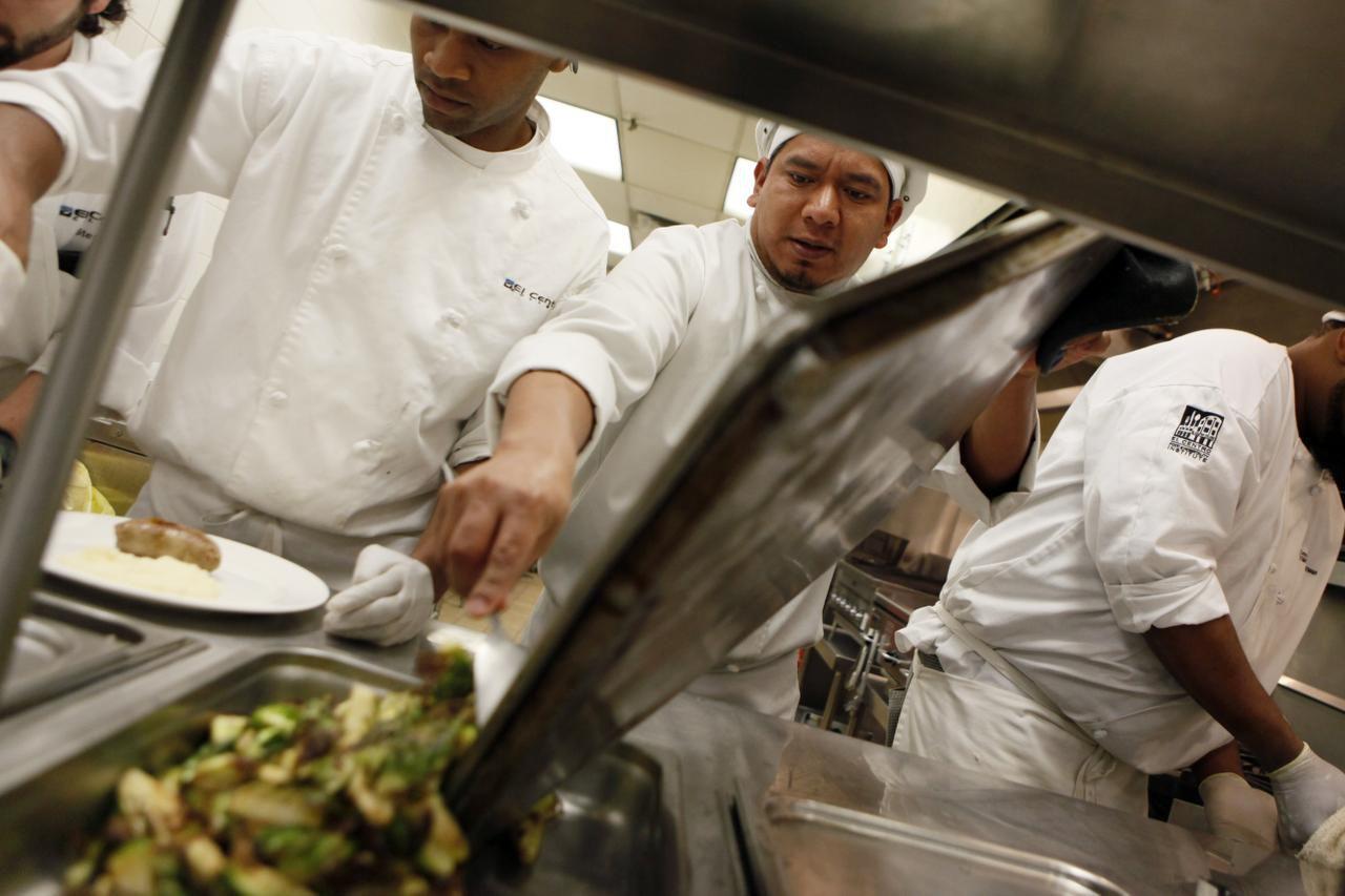 Alfonso González (centro), sirve unas coles de bruselas asadas, durante una de sus prácticas culinarias en El Centro. (ESPECIAL PARA AL DÍA/BEN TORRES)