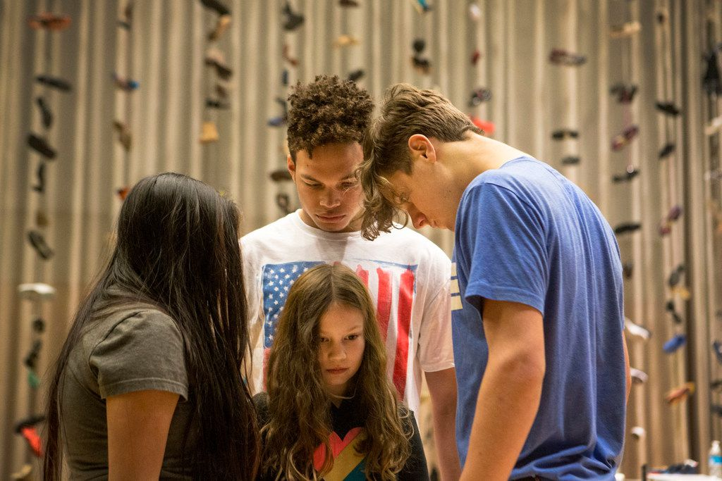 From left: Regina Juarez, 18; Jordan Mercado, 18; and Joshua Bowman, 16, surround Maren Bennett, 10, during a rehearsal of Cry Havoc Theater's Babel, at the Winspear Opera House in Dallas on June 30. The teen theater company was practicing for their show focusing on gun violence.