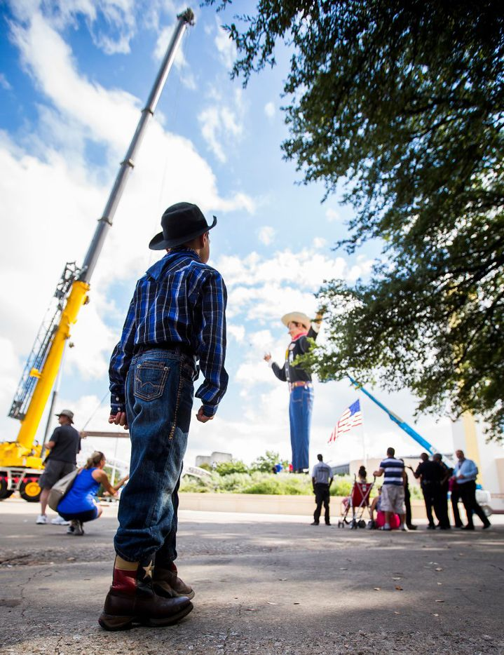 Chistopher Hoffman, 7, dresses the part as he watches workers install Big Tex in Fair Park on Friday, Sept. 23, 2016, in Dallas. The State Fair of Texas opens on September 30 and runs through October 23. (Smiley N. Pool/The Dallas Morning News)