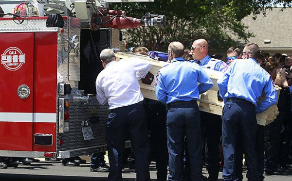 Brownwood firefighters load the casket of Lt. Shannon Stone onto a fire truck following Stone's funeral service Monday at First United Methodist Church of Brownwood. Stone died last week after falling from the outfield stands at Rangers Ballpark in Arlington.