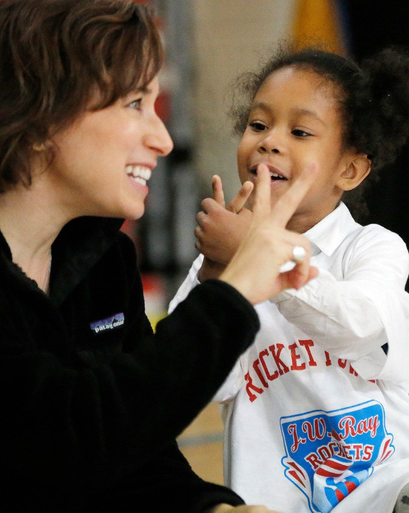 Angela Barnhart, of Looney and Associates, asks Kileigh Williams, 5,   how many siblings she has after donating supplies, office furniture to help redecorate two teacher lounges, provide a new laundry washer and dryer and sports equipment at JW Ray Elementary School.