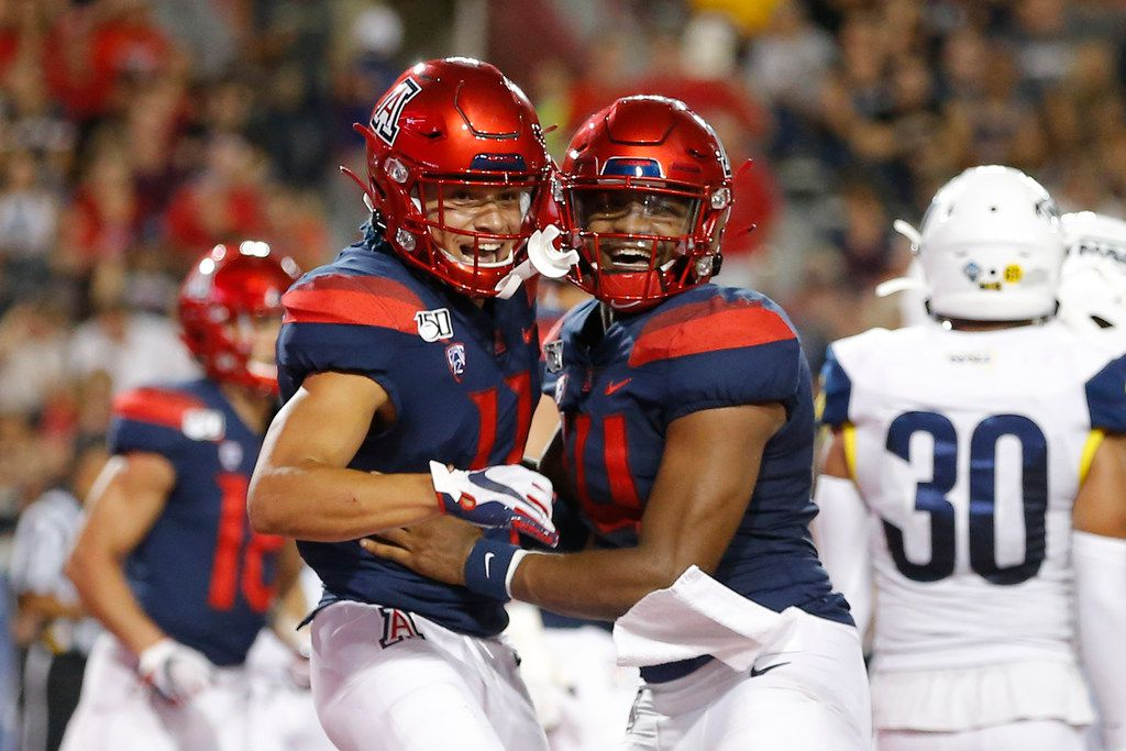 Arizona wide receiver Tayvian Cunningham (11) celebrates with Khalil Tate (14) after scoring a touchdown against Northern Arizona in the first half during an NCAA college football game, Saturday, Sept. 7, 2019, in Tucson, Ariz.