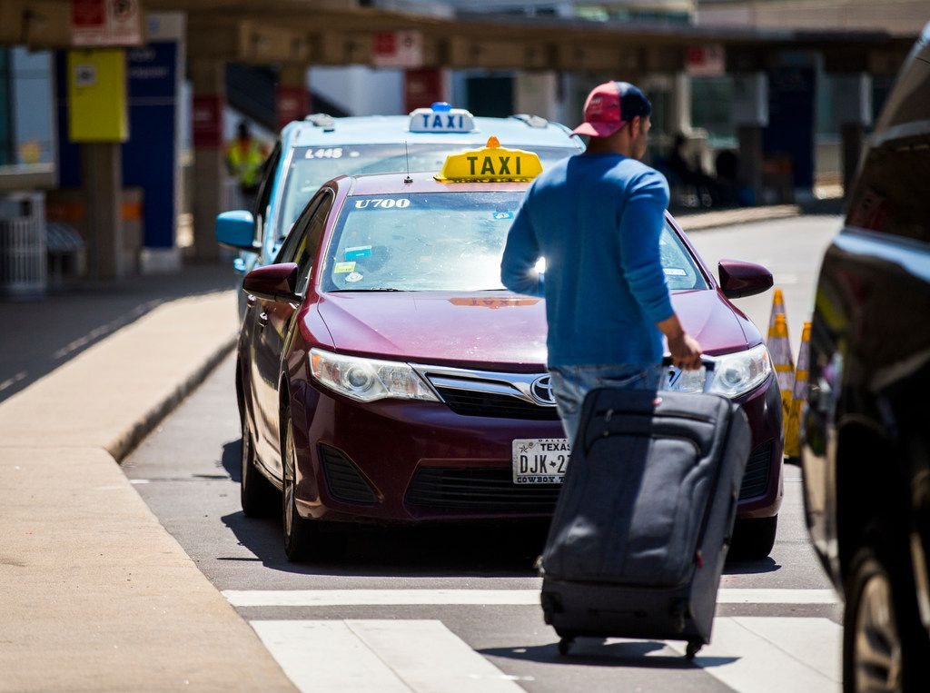 A traveler passes taxi cabs waiting for customers at Terminal A at DFW International Airport.