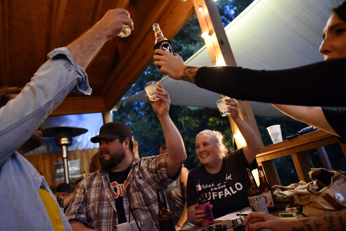 Mikhail Morales (left) and April Benzel raised their drinks to toast the start of the Ten Bells pub quiz at Ten Bells Tavern in the Bishop Arts District in August 2017.