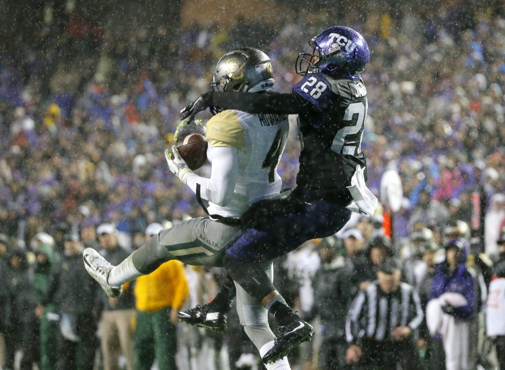 Baylor cornerback Xavien Howard, left, intercepts a pass intended for TCU wide receiver Tony James, right, in the first half of an NCAA college football game, Friday, Nov. 27, 2015, in Fort Worth, Texas.