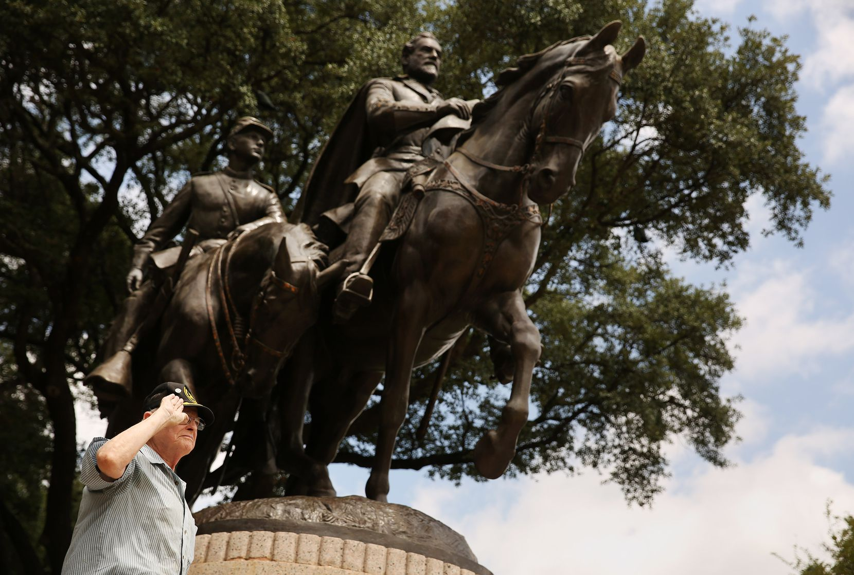 """A visitor gives the """"palm out"""" Confederate salute while being photographed at Robert E. Lee Park in the Oak Lawn neighborhood of Dallas Aug. 16, 2017."""