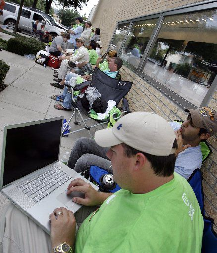 Ashton Smith works on his computer as he waits in line to buy the original iPhone on June 29, 2007, outside the Apple Store on Knox Street in Dallas.