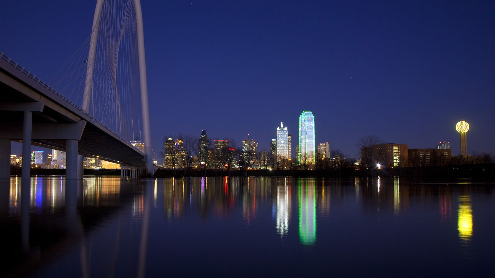 Spanning the flooded Trinity River between downtown and West Dallas, the Margaret Hunt Hill Bridge is seen as the river crests at dusk, Thursday, January 26, 2012.  A significant rainfall filled the river bottom from bank-to-bank. World-renowned architect Santiago Calatrava designed the bridge. Reunion Tower is at far right. (Tom Fox/The Dallas Morning News)