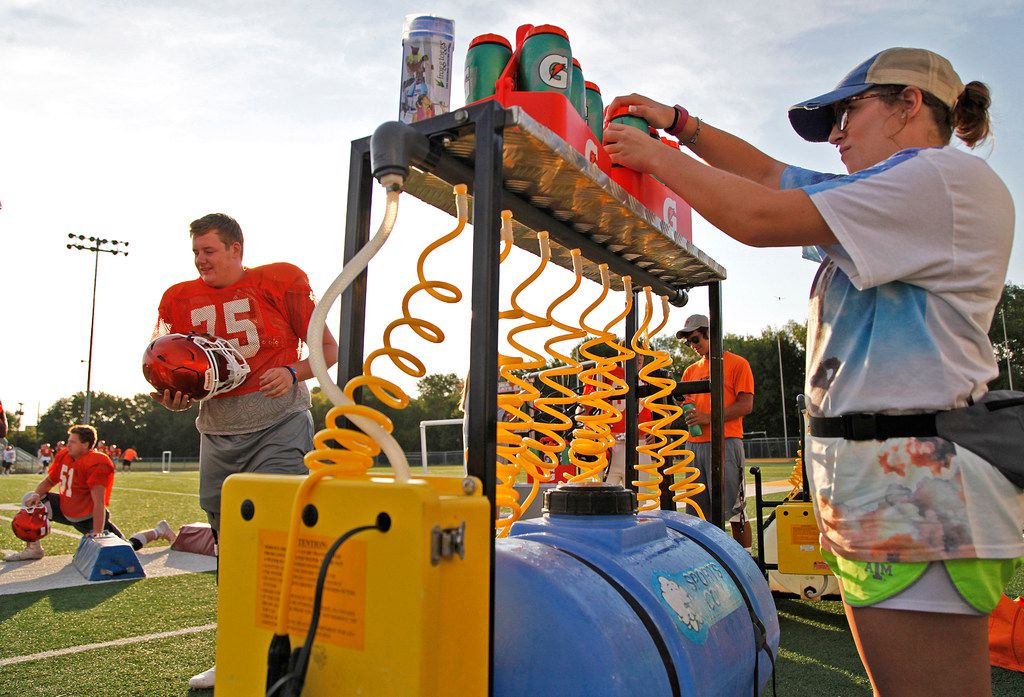 Student athletic trainer Jamie Owen (right), 16, prepares a water station before practice as offensive lineman Trenton Williams (75) takes the field during the first week of football practice for Celina High School at Bobcat Stadium on Wednesday, August 8, 2018. (Stewart F. House/Special Contributor)