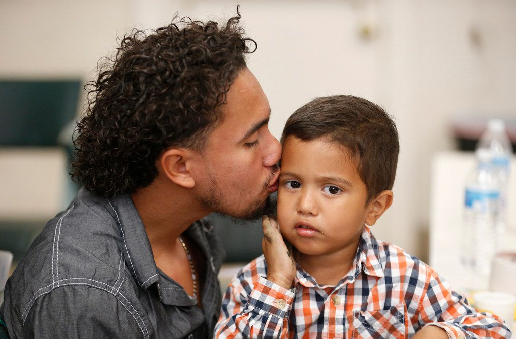 Roger Ardino 24, gives his son Roger Ardino Jr., 4, a kiss on the cheek shortly after speaking to reporters at a news conference at the Annunciation House in El Paso on Wednesday, July 11. Ardino and Pablo Ortiz, 28, and his son Andres 3, spoke to the media about their experiences while being detained and separated for several months from their sons.