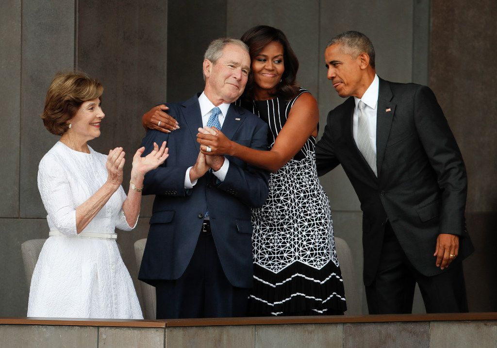 First lady Michelle Obama (center) hugs former President George W. Bush, as President Barack Obama and former first lady Laura Bush walk on stage at the dedication ceremony of the Smithsonian Museum of African American History and Culture on the National Mall in Washington on Sept. 24, 2016.