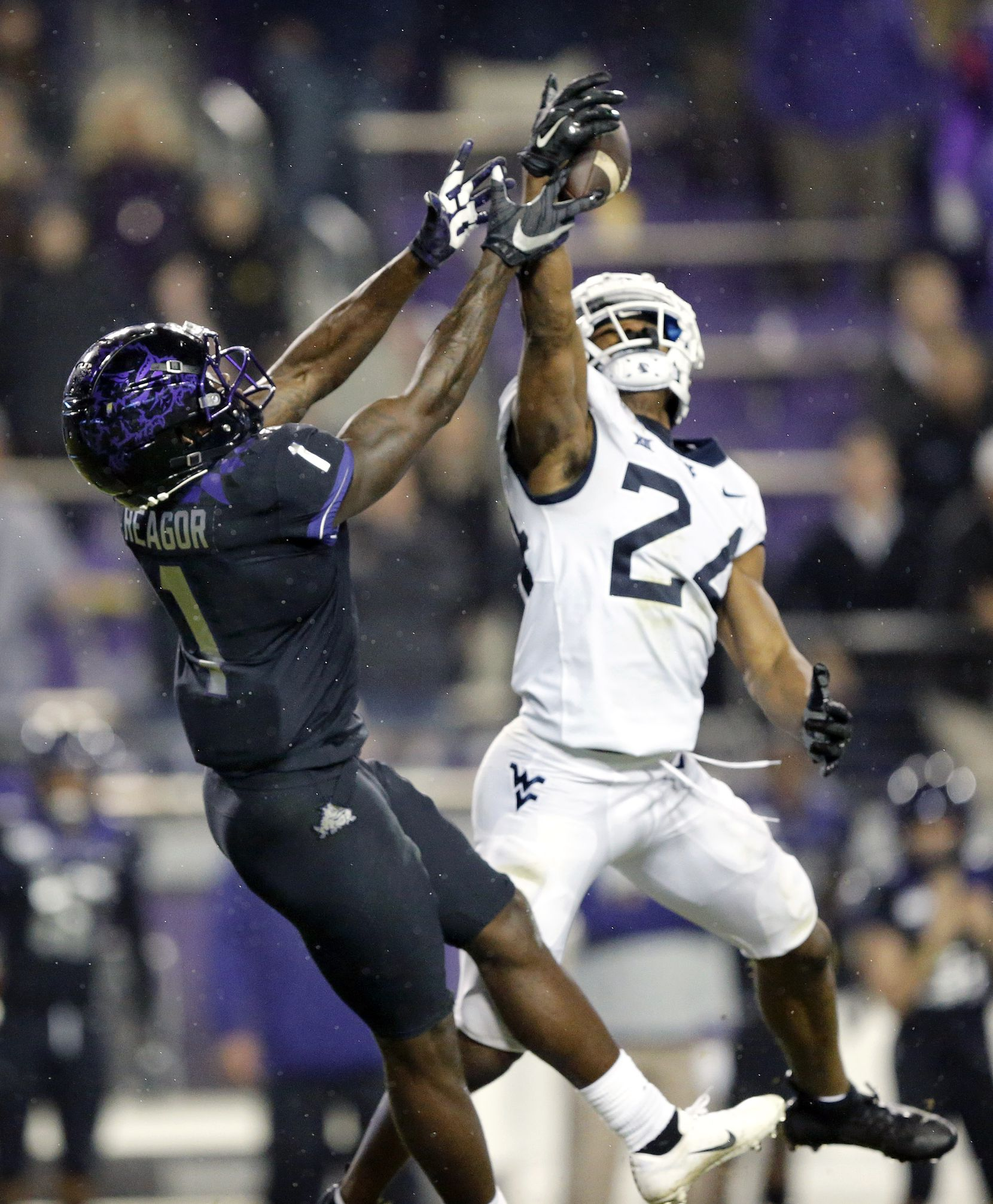 West Virginia Mountaineers cornerback Hakeem Bailey (24) swats away a long fourth quarter pass intended for TCU Horned Frogs wide receiver Jalen Reagor (1) at Amon G. Carter Stadium in Fort Worth, Friday, November 29, 2019. The Horned Frogs lost, 20-17.