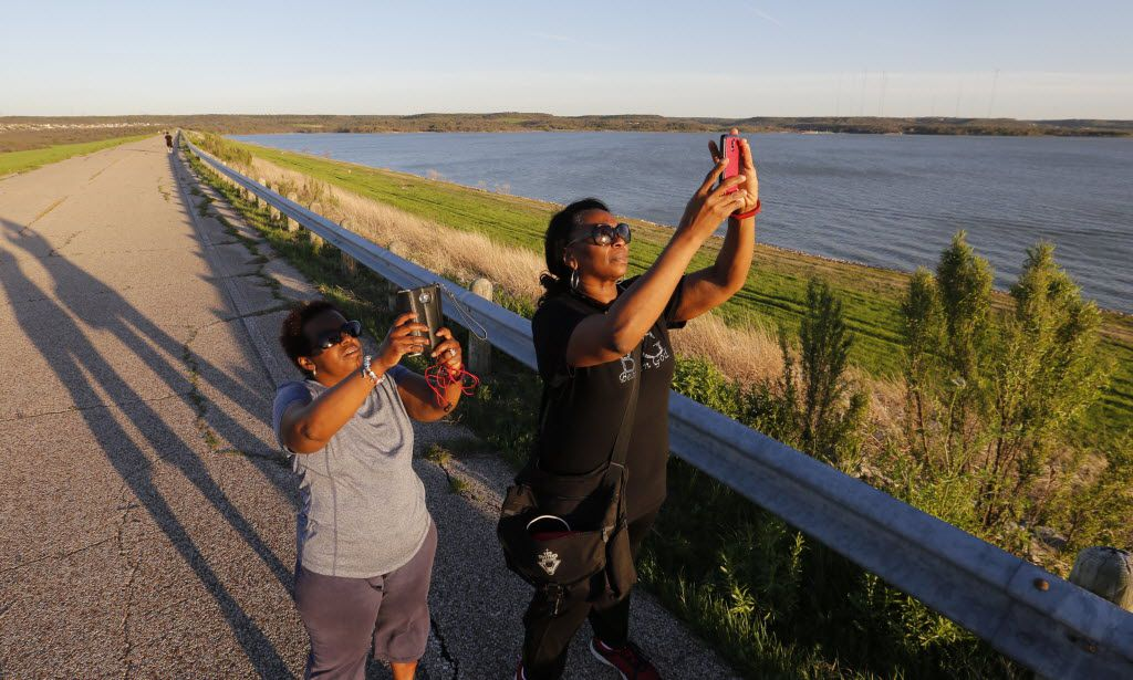 Amina Duncan and Victouria (cq) Lecoq take photos of the setting sun from the dam at Joe Pool Lake Tuesday evening March 15, 2016. Mansfield Road serves as a path for the cyclist and pedestrian.(Ron Baselice/The Dallas Morning News)
