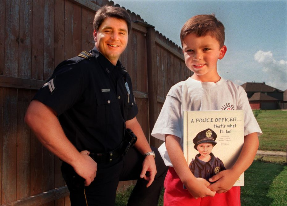 ORG XMIT: S11A47F11 Dallas police Senior Cpl. Ronald Pinkston with his son Trevor Pinkston, 6, who holds a book his father wrote for him.  Cpl. Pinkston,37, wrote the book about a child who wishes to become a police officer and published it using a significant amount of his own money.  They are in the backyard of their Rowlett home. Trevor's likeness is on the cover of the book. 06202013xNEWS