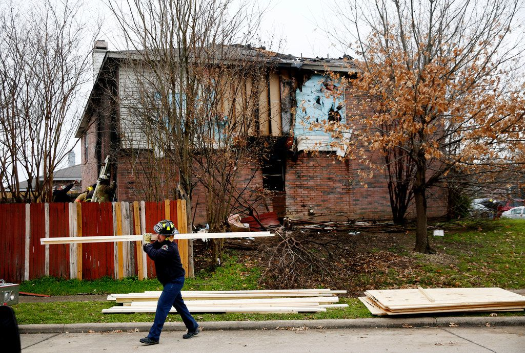Dallas and Cedar Hill fire-rescue personnel reinforce a house that caught fire early Thursday morning. Three people died in the home in the 700 block of Lovern Street in Cedar Hill.