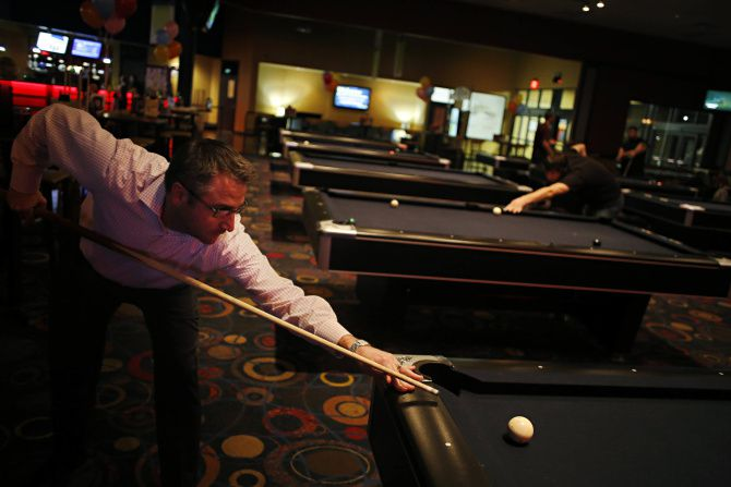 Darin Lyons lines up a shot while playing pool at Main Event in Frisco. Today's entertainment attraction isn't just bowling and billiards anymore.