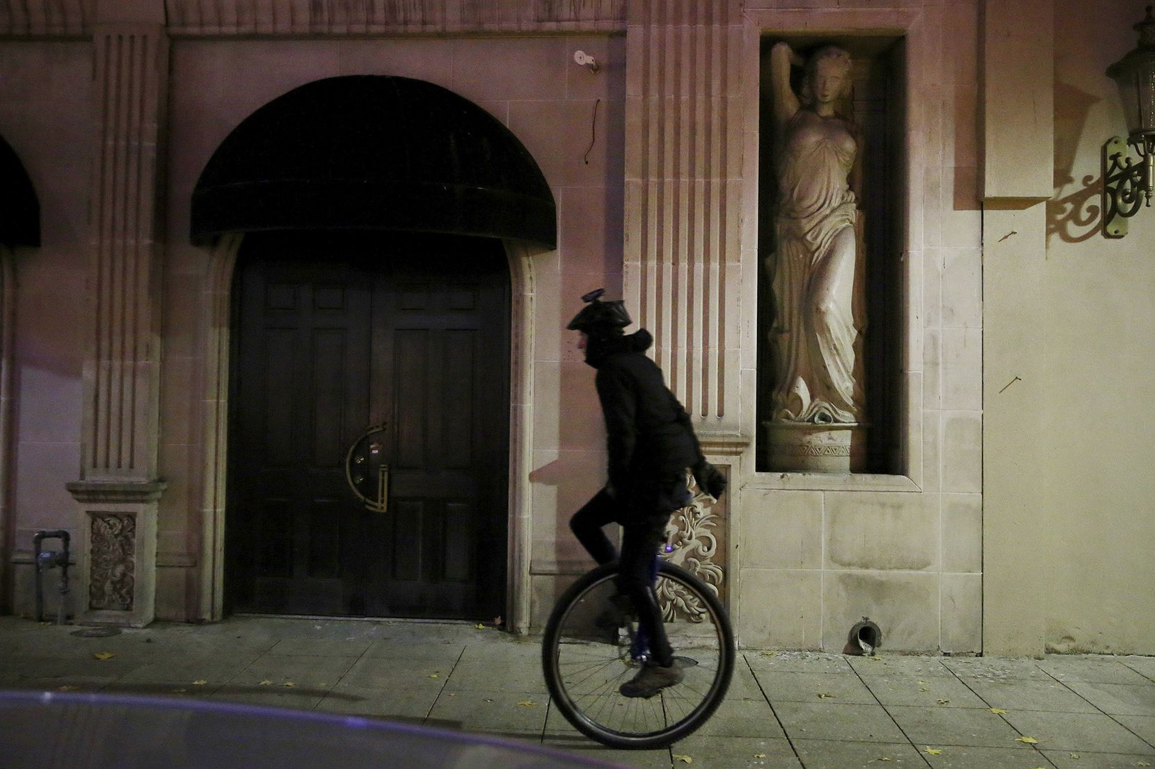 A unicyclist rides near 1400 Main Street in downtown Dallas on Sunday night.