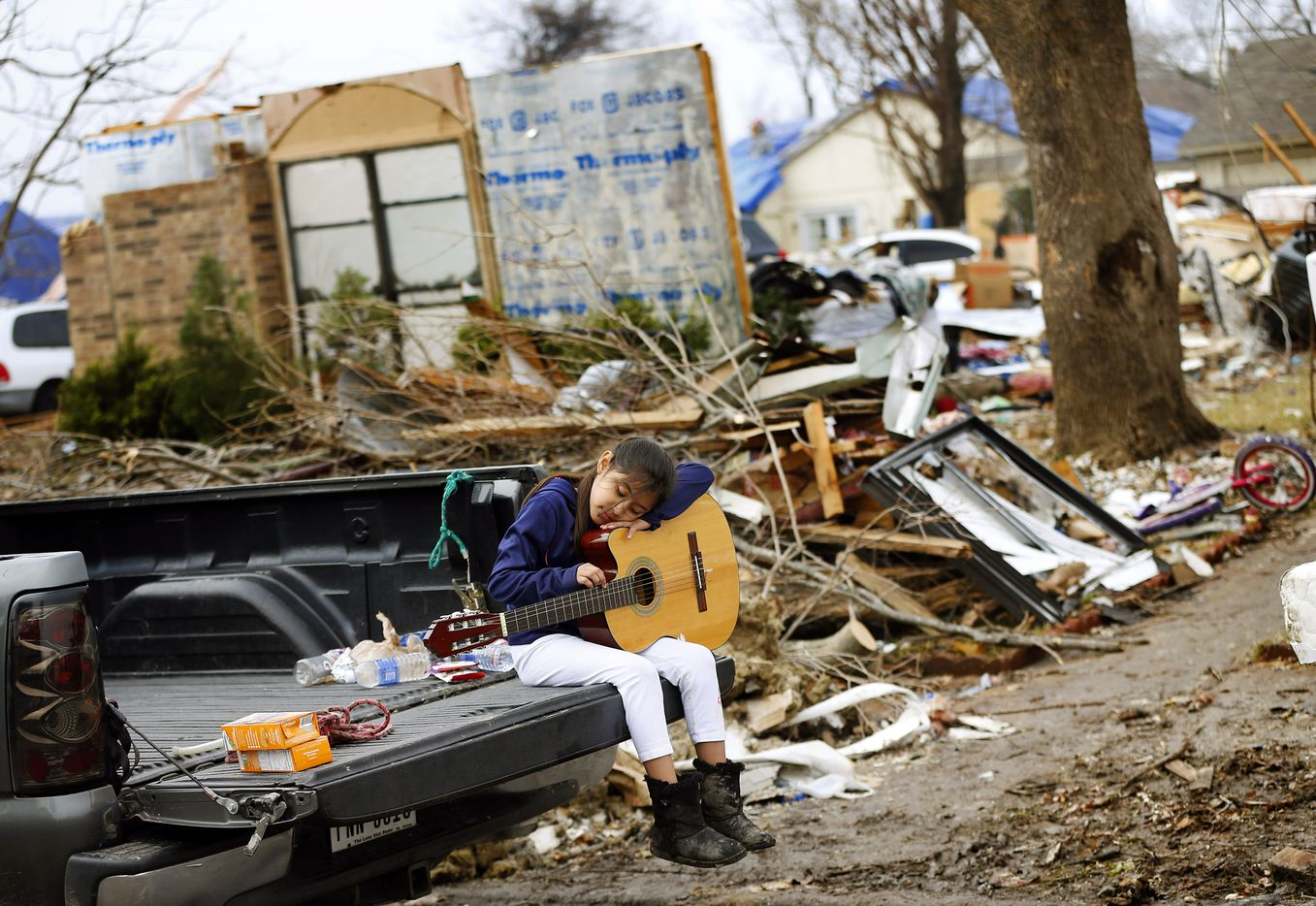 Natalie Rojas, 8, strums a guitar found in the bedroom of her tornado damaged home on Mariner Drive in Rowlett on Jan. 8, 2016. Volunteer groups continued to clean up the tornado-ravaged neighborhood off Schrade Road. The guitar was a gift from her uncle.