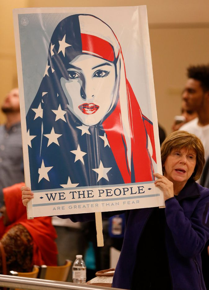 Cheryl Pollman holds a sign during a DFW Airport protest against a White House order banning refugees and legal immigrants from entering the U.S.