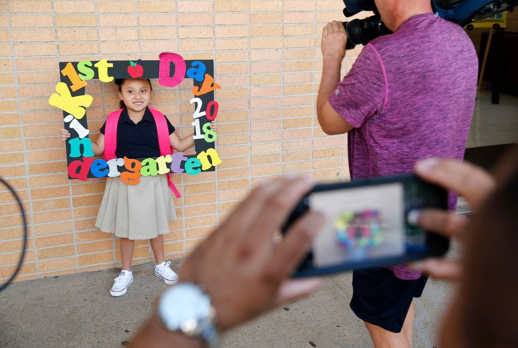 Kindergartner Roseann Arellano, 5, poses with her sign for her father, Juan Arellano on the first day of school at L.O. Donald Leadership Academy in Dallas on Aug. 20, 2018.