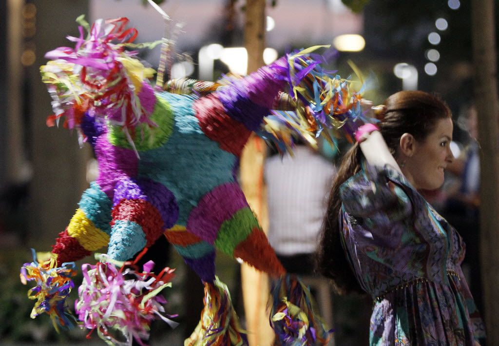 Hilary L. Roberts takes whack at a pinata for charity during Mission Ole benefiting Trinity River Mission at One Arts Plaza in Dallas, Saturday, September 27, 2014. (Brandon Wade/Special Contributor) 10052014xMETRO