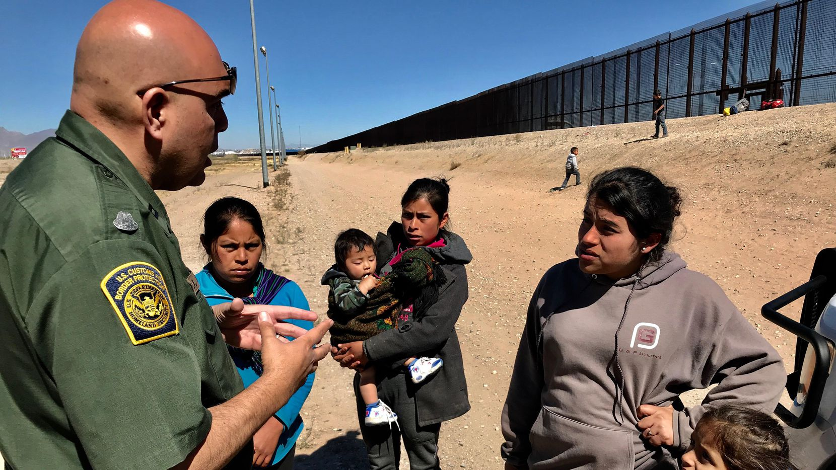 Familias de inmigrantes se entregan a oficiales de la Patrulla Fronteriza en la frontera entre El Paso y Ciudad Juárez. (DMN/ALFREDO CORCHADO)