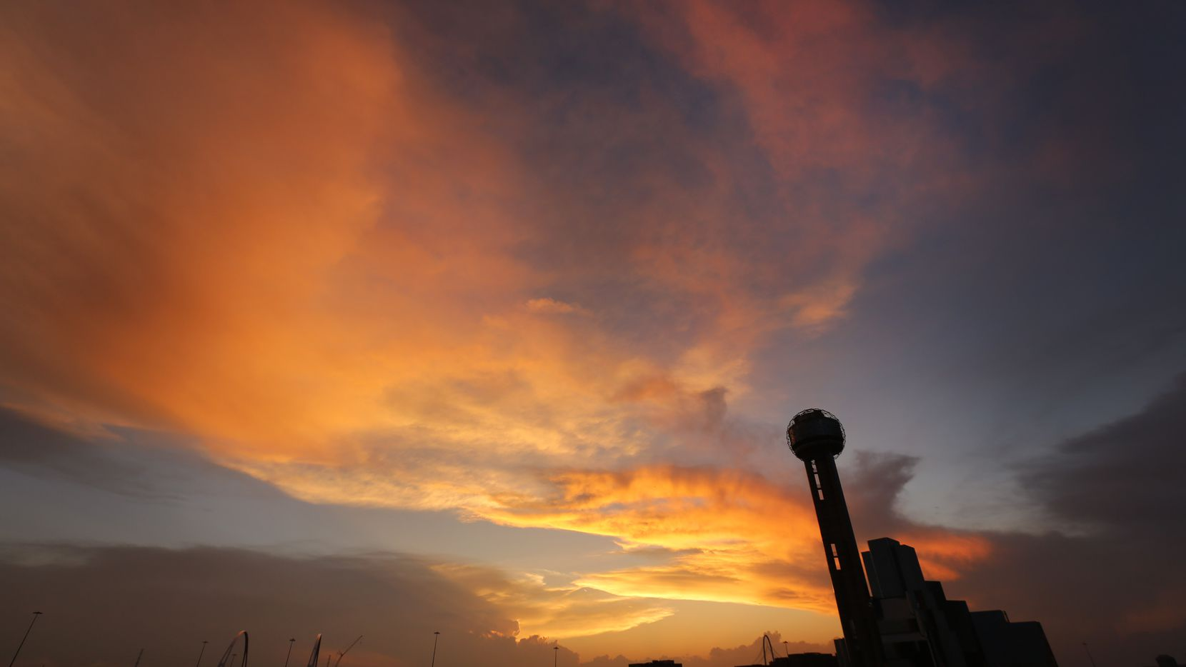The sun sets behind Reunion Tower as approaching storms loom on the horizon, Friday evening, April 21, 2017. Storms are expected later tonight with a passing cold front.  (Tom Fox/The Dallas Morning News)