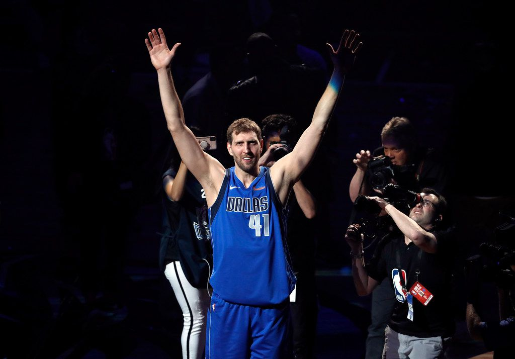 Dallas Mavericks' Dirk Nowitzki acknowledges cheers from fans as he walks off the court following the team's NBA basketball game against the Phoenix Suns in Dallas, Tuesday, April 9, 2019. The team honored Nowitkzi, who played his final home game of his 21-year career. (AP Photo/Tony Gutierrez)