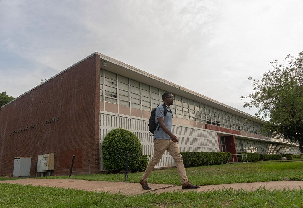 Cameron Johnson, a business student at Paul Quinn College, walks past a building that will be renovated into a 40,000-square-foot educational and residential building.  It will be named after one of the university's biggest benefactors, Dallas businessman and environmentalist Trammell S. Crow.