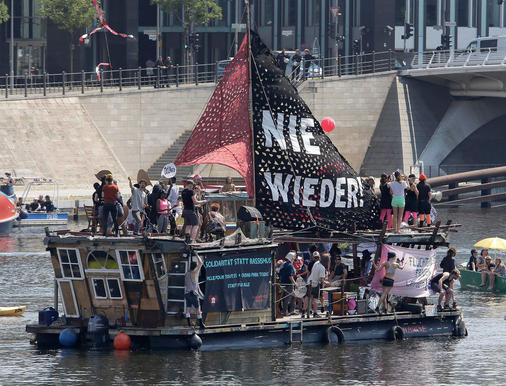 Activists protest against racism on a ship on the Spree river in Berlin, Germany, Sunday, May 27, 2018. The AfD that swept into Parliament last year on a wave of anti-migrant sentiment is staging a march through the heart of Berlin to protest against the government.