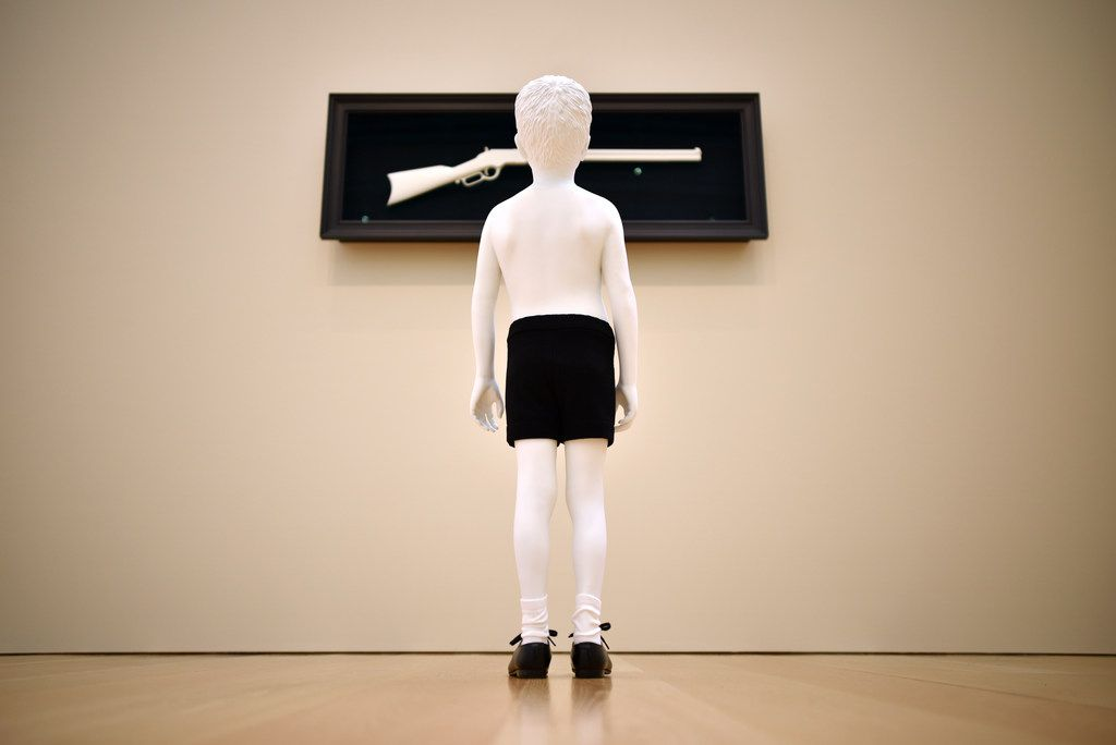 In One Day, a shirtless boy gazes up at a rifle mounted on the wall. The artists say that the piece speaks to the way that people become fascinated with objects. We see something, and we want it — especially if the object is powerful or dangerous.