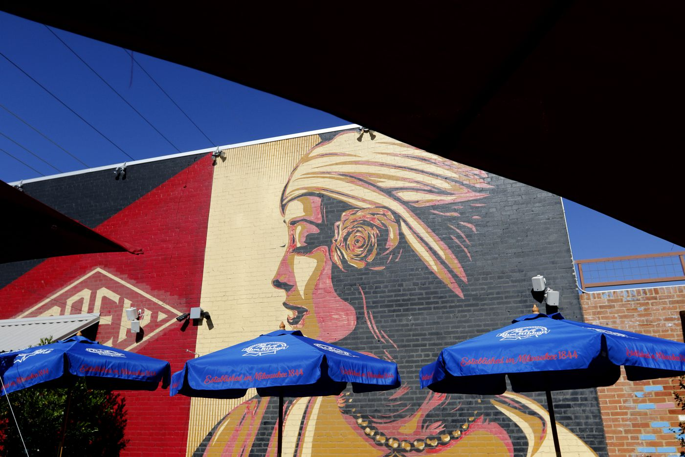 A mural, painted by graffiti artist Shepard Fairey, on the east side of the Off-Site Kitchen building in Trinity Groves