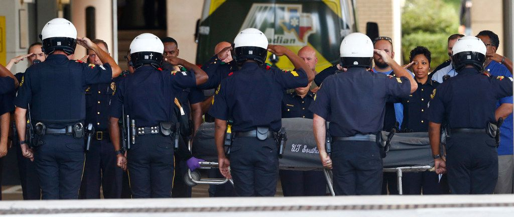 """Dallas Police and Chief U. Renee Hall salute as they transport Senior Cpl. Earl """"Jamie"""" Givens' body after he was killed in a motorcycle crash with an SUV on Interstate 20. Photo taken at Baylor University Medical Center at Dallas on July 21, 2018. (Nathan Hunsinger/The Dallas Morning News)"""