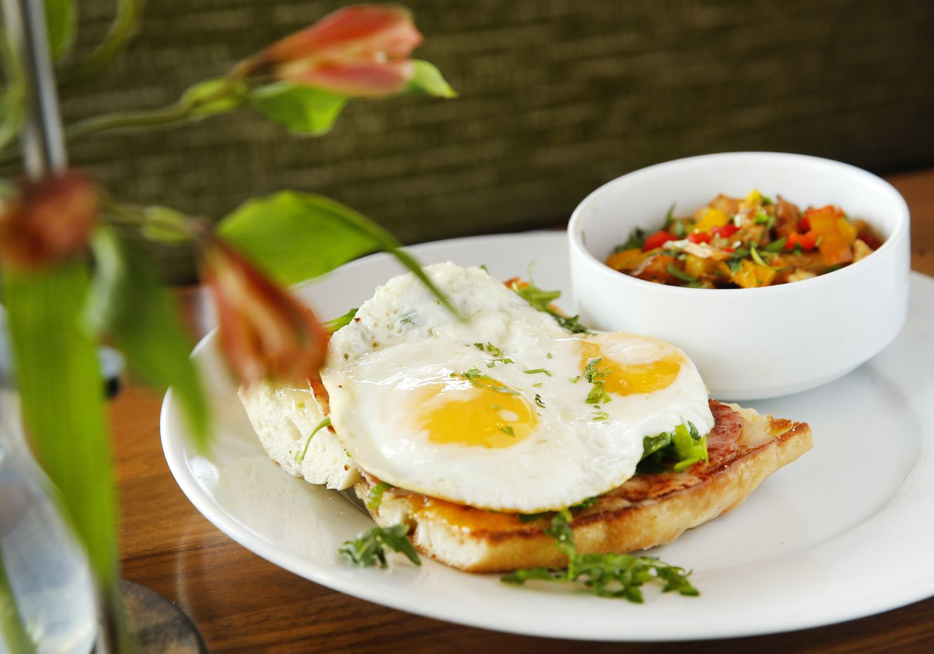 The open-faced sandwich is a local baguette with two fried eggs, all-natural ham swiss and arugula at Bellagreen. It is served with a side of potatoes O'Brien.