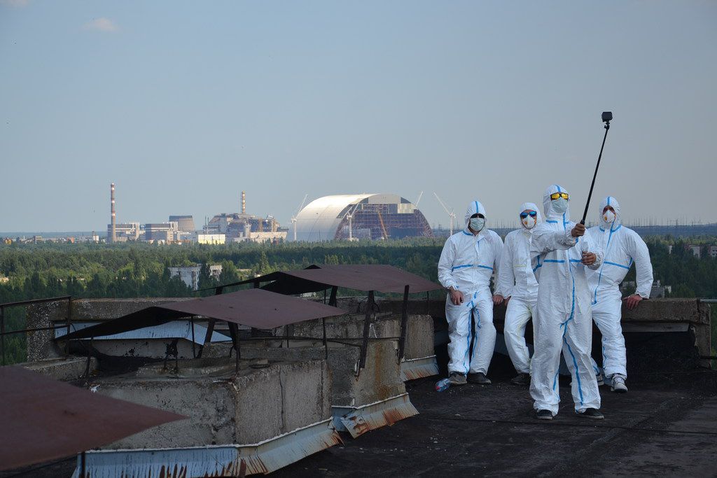 Visitors take a rooftop selfie with the Chernobyl nuclear power plant in the background. Most visitors opt for regular attire.