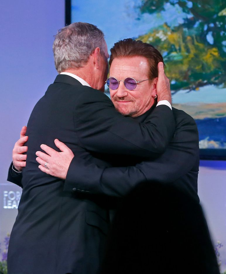 Former President George W. Bush hugs Bono, a recipient of the George W. Bush Medal for Distinguished Leadership, during the Forum on Leadership Gala at George W. Bush Presidential Center in Dallas on April 19, 2018.